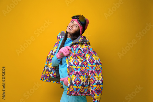 Woman wearing stylish winter sport clothes on yellow background