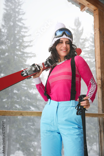 Young woman with skis wearing winter sport clothes outdoors