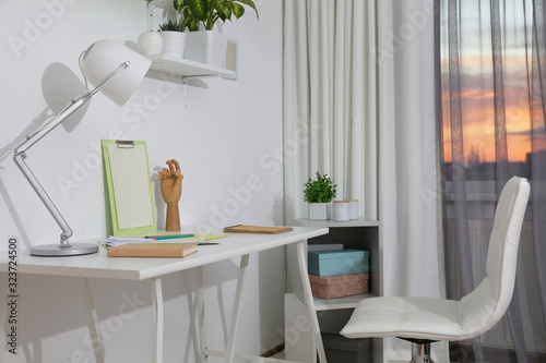Stylish room interior with comfortable workplace near window. Design idea