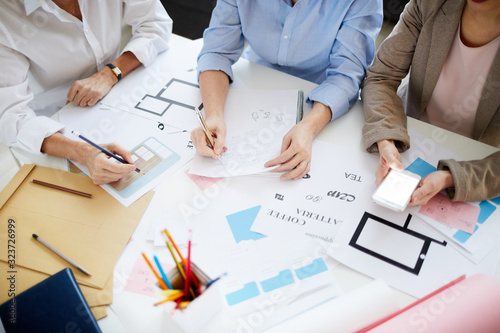Fotografía High angle shot of three unrecognizable designers collaborating on project