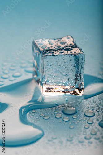 Ice cube with water drops on a blue background. The ice is melting.