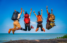 Group Of People Jumping On Mountain Top Cliff Edge. Happy Traveler Jumping With Backpack Travel Lifestyle Adventure Concept. Active Summer Vacations Outdoor On Mountains Success And Fun