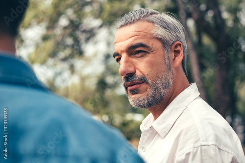 Portrait of handsome Caucasian older man talking with friend or his son at park, Fototapete