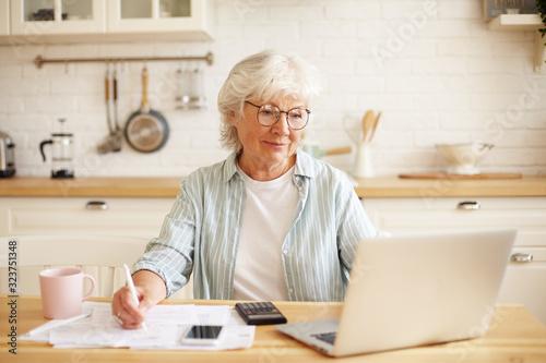 Valokuva Attractive positive senior mature female in glasses sitting at kitchen counter i