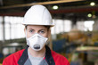 canvas print picture - Horizontal close up head and shouldres portrait of unrecognizable female factory worker wearing protective helmet and mask