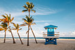 canvas print picture - Beautiful tropical Florida landscape with palm trees and a blue lifeguard house. Typical American beach ocean scenic view with lifeguard tower and exotic plants. Summer seasonal wallpaper background.