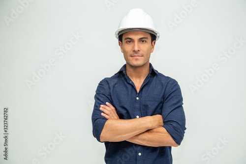 Fotografiet Handsome man industrial engineer wearing a white helmet solated on white backgro