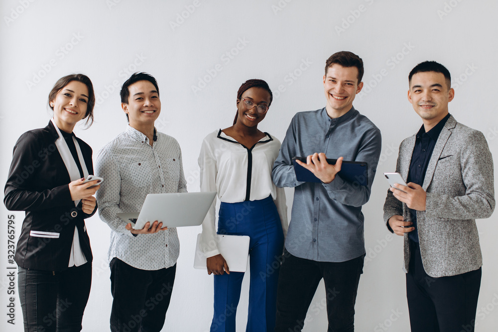 Fototapeta Group of multicultural young executive people standing and busy using smartphones for work in the office. Social media technology and online business with teenager lifestyle concept