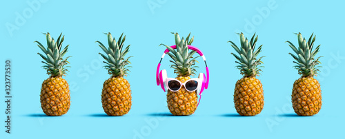 Fototapeta One out unique pineapple wearing headphones on a solid color background obraz