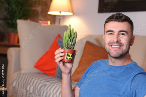 Man using a cactus to absorb radiation at home Canvas Print