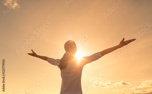 Obraz na plátně Happy positive woman looking up to the sunset sky with arms up feeling free