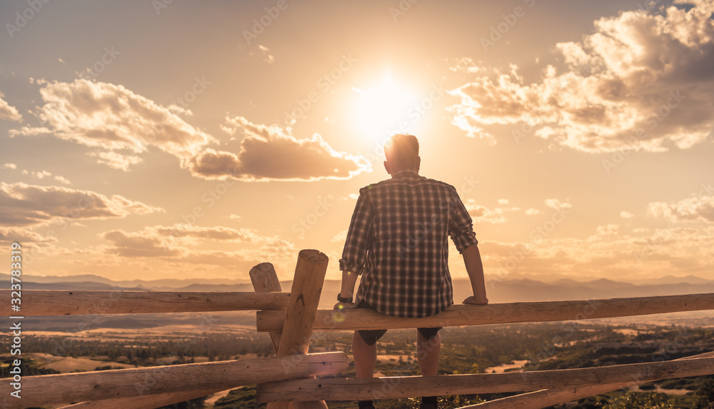 Fototapeta Young man sitting looking at the the beautiful view. Getting away from it all, people relaxing in nature concept.