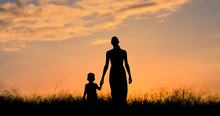 Mother Holding Childs Hand Walking Through A Field At Sunset.
