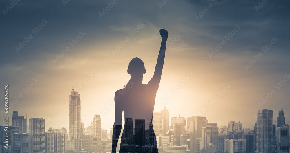 Fototapeta confident young woman with fist in the air facing the city. People power and strong young woman concept