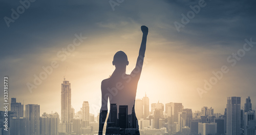 Fotomural confident young woman with fist in the air facing the city