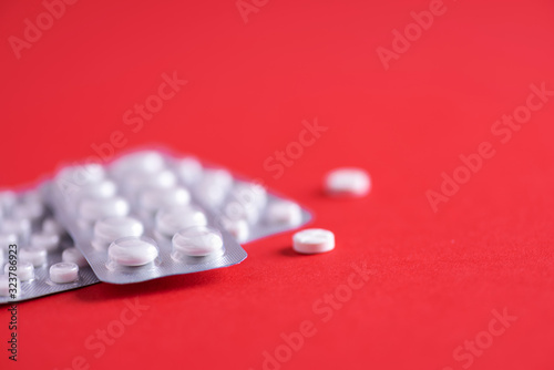 Photo Many white capsule in blister package on red background