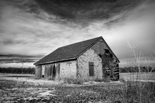 Black And White Shot Of An Old Dilapidated Abandoned Farmhouse On The Missouri Prairie.