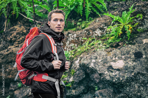 Hiker man hiking in rainforest spring autumn. Male hiker looking away walking in outdoors forest nature trail path. Caucasian male model on adventure trek wearing rain jacket and camping backpack.