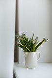 Green flowers in a white ceramic vase on a wooden board white windowsill in cozy interior
