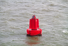 A Red Buoy Is Floating On The Grey Water Surface In The Dutch Wadden Sea