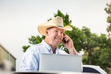 Farmer With Cowboy Hat Talking On Phone And Working On Computer. Montana, USA