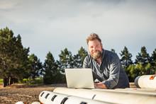 Surveyor In Field Entering Data Into Laptop. Bridger, Montana, USA