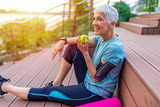 Portrait of a beautiful older woman with green healthy food after workout. Portrait of fit mature woman smiling while holding an apple and bottle of water. Sporty senior woman