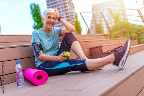 Senior woman eating apple after exercise Lerretsbilde