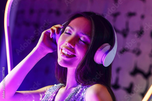 Toned portrait of young woman with headphones on dark color background
