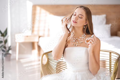 Beautiful young bride with bottle of perfume at home