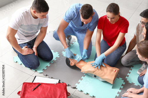 Instructors demonstrating CPR on mannequin at first aid training course