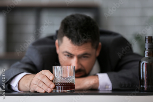 Businessman drinking cognac in office. Concept of alcoholism