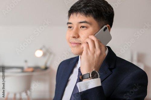 Young Asian businessman talking by phone in office