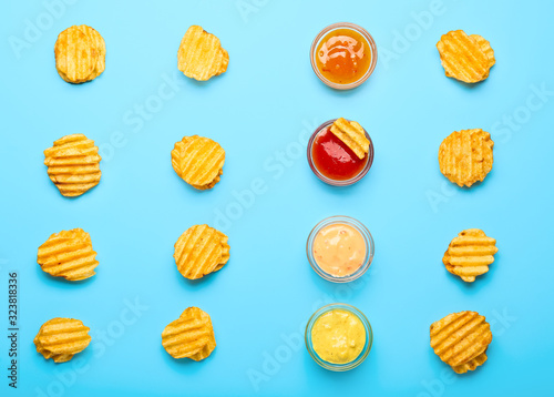 Tasty potato chips and sauces on color background