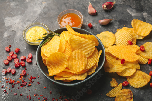 Bowl with tasty potato chips on table