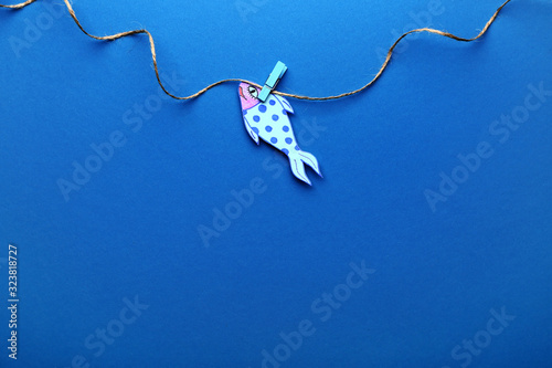 Paper fish on color background. April Fool's Day prank