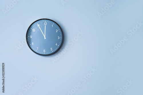 Clock hanging on color wall
