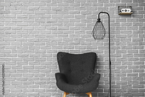 Armchair and lamp near brick wall in room