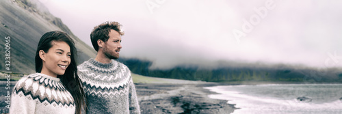 Fotografie, Obraz Winter nature panoramic people couple wearing icelandic wool handknit knitted pullover sweaters on outdoor beach banner
