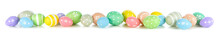 Easter Eggs Scattered Forming A Long Border Isolated On A White Background. Pastel Colors.