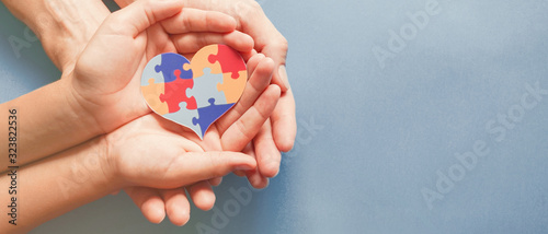 Obraz Adult and chiild hands holding jigsaw puzzle heart shape, Autism awareness,Autism spectrum disorder family support concept, World Autism Awareness Day - fototapety do salonu