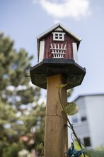 Vertical Shot Of A Wooden Birdhouse On A Blurred Background