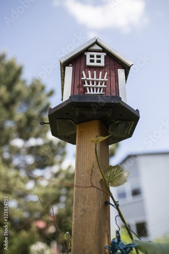 Canvas-taulu Vertical shot of a wooden birdhouse on a blurred background