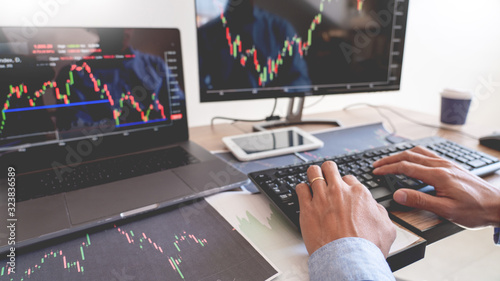 Obraz Working business man, team of broker or traders talking about forex on multiple computer screens of stock market invest trading financial graph charts data analysis. - fototapety do salonu