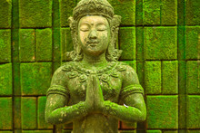 Stucco Figure, Carved Stone Buddha Head Statue The Face Of A Holy Angel In Buddhism Was Placed Outdoors In The Midst Of Moisture And Green Moss