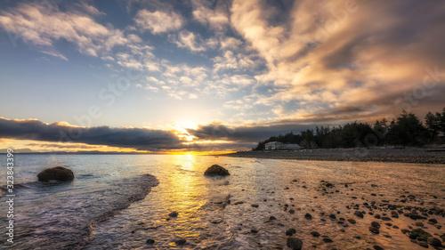 Fototapeta Beautiful sunrise under dramatic clouds along a shore with a lone house. obraz na płótnie