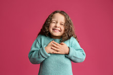 Cute Grateful Little Girl With Hands On Chest Against Pink Background