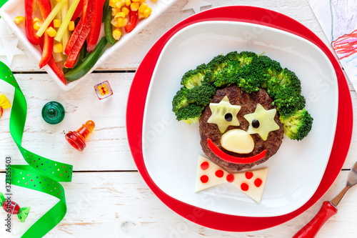 Fototapeta Fun food for kids - cute smiling face of a funny clown made of meat burger, broccoli and cheese. Healthy eating for children obraz
