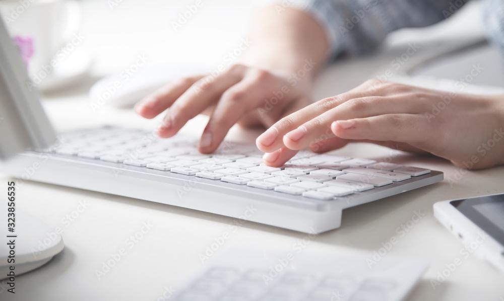 Fototapeta Hands typing on computer keyboard in office desk.
