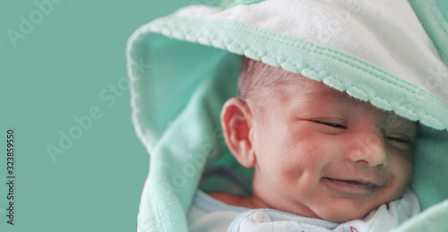 Vászonkép a smiling newborn baby with dimple in cheek wrapped in sea green colored towel w